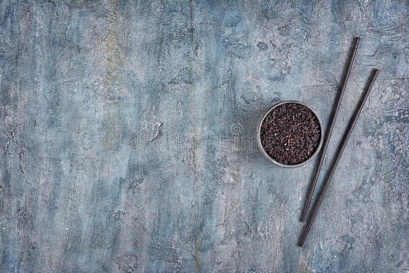 Schüssel ungekochter schwarzer Reis mit hölzernen chinesischen Essstäbchen lizenzfreie stockfotografie