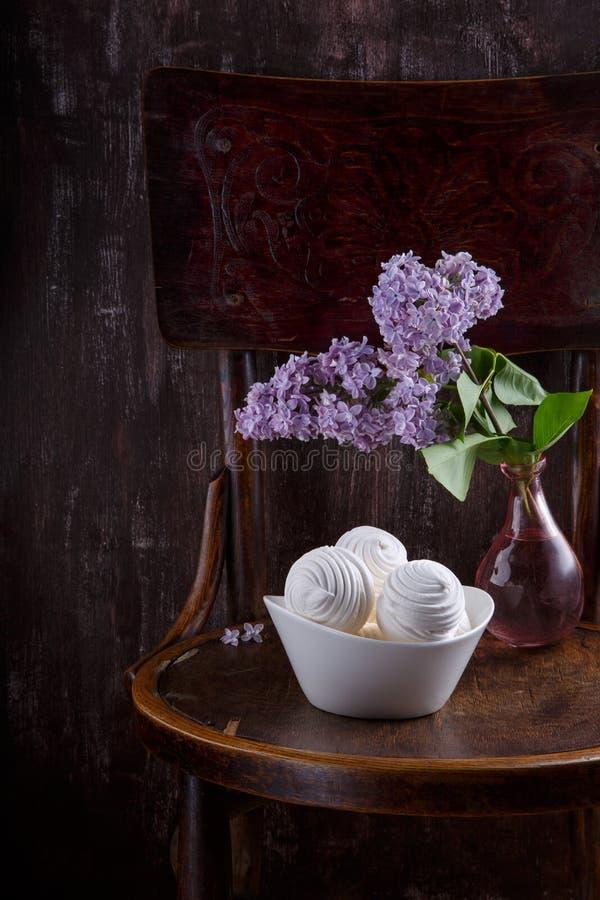 Schüssel weiße Zefireibische und Blumenstrauß von lila Blumen auf altem Weinlesestuhl Stillleben auf dunklem Hintergrund stockfoto