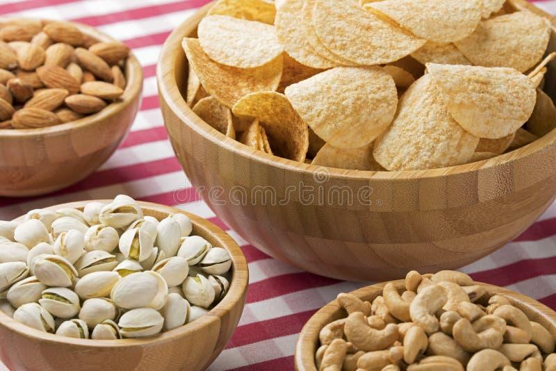 Schüsseln Kartoffelchips, Mandeln, Pistazien, Acajoubäume auf roter Kontrolle lizenzfreies stockfoto