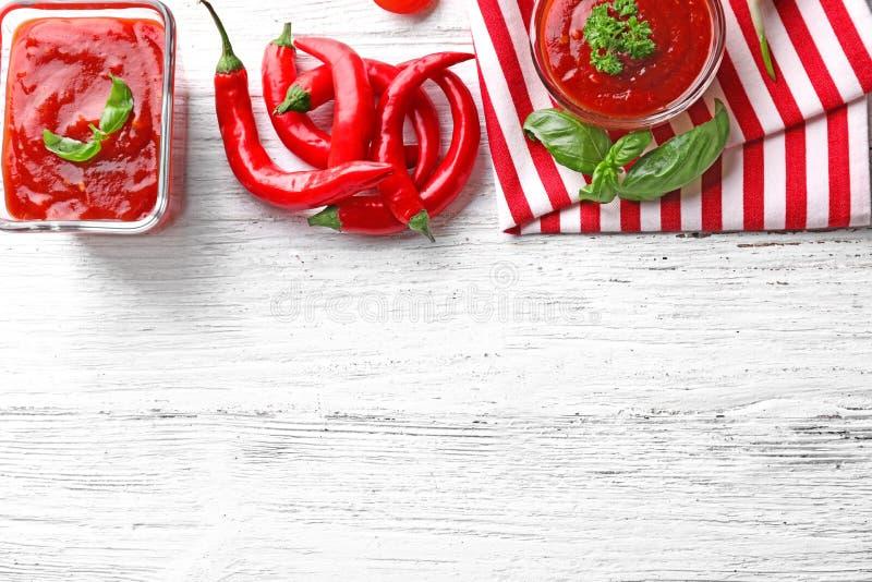 Schüsseln mit köstlicher Tomatensauce und Paprikapfeffern auf Holztisch stockbild