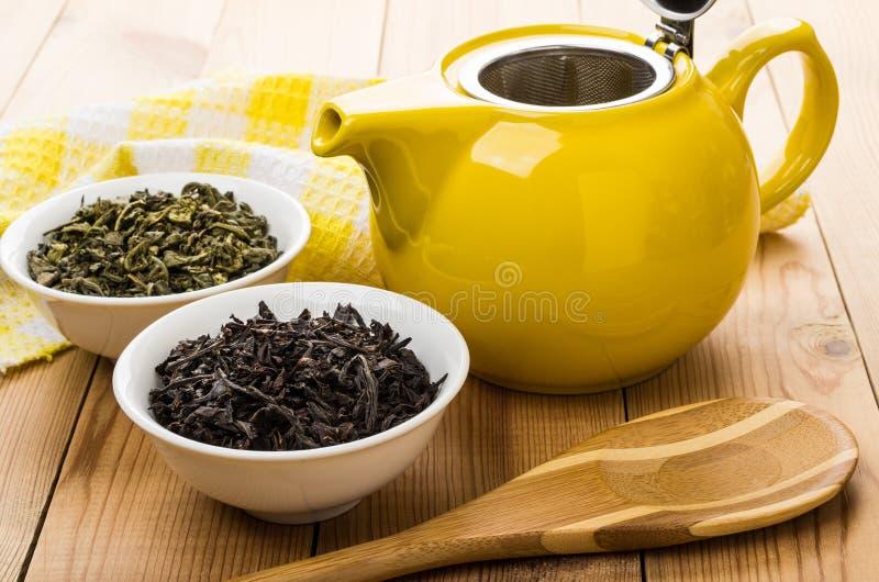 Schüsseln mit trockenem grünem und schwarzem Tee, Teekanne, Löffel lizenzfreie stockbilder