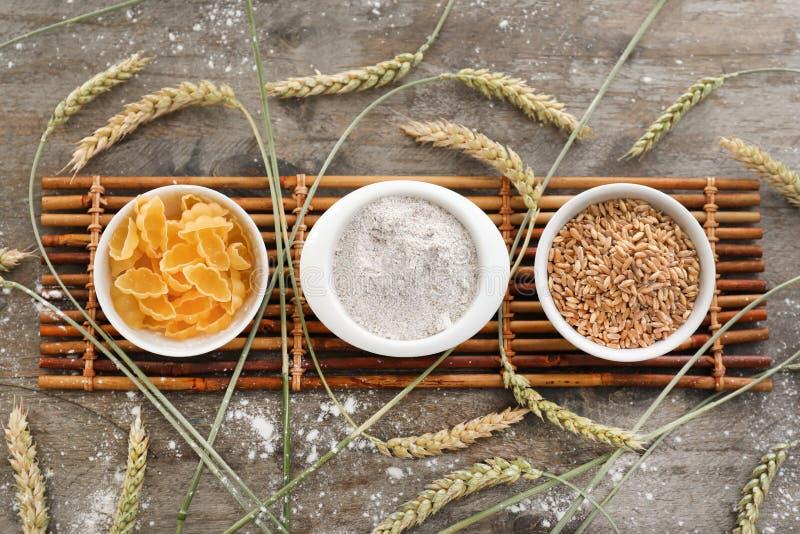 Schüsseln mit Weizenmehl, -körnern und -teigwaren auf Holztisch lizenzfreies stockfoto