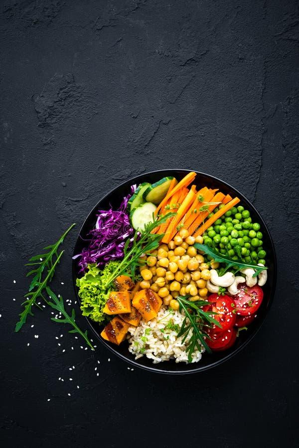 Schüsselteller mit Naturreis, Gurke, Tomate, grünen Erbsen, Rotkohl, Kichererbse, frischem Kopfsalatsalat und Acajounüssen Gesund stockfotografie