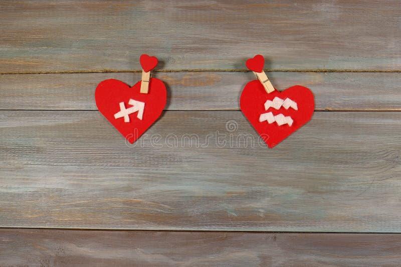 Schütze und Wassermann Zeichen des Tierkreises und des Herzens hölzern stockbilder