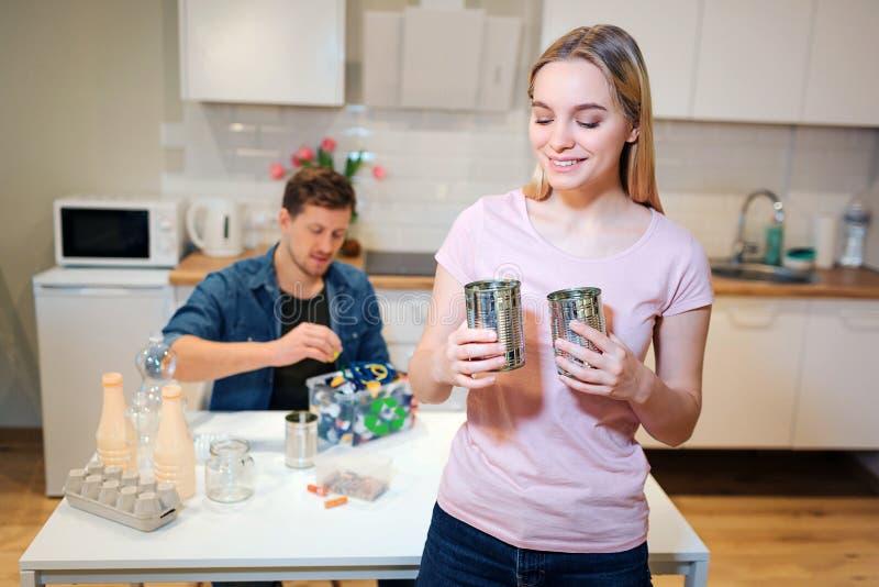 Schützen Sie die Umgebung Junge lächelnde Frau, die Metallblechdosen für Wiederverwendung während ihr Ehemann an sortiert den Abf lizenzfreie stockbilder