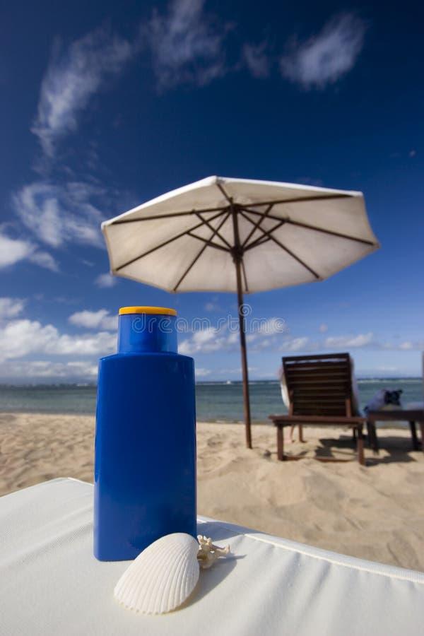 Schützen Sie sich vor Sonne auf dem Strand mit bräunendem Schmieröl lizenzfreie stockbilder