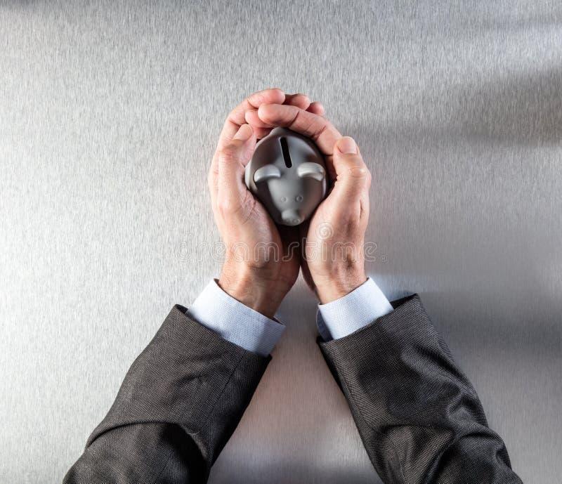 Schützender Geschäftsmann übergibt das Halten eines sicheren Geldkastens für Reichtum stockbild