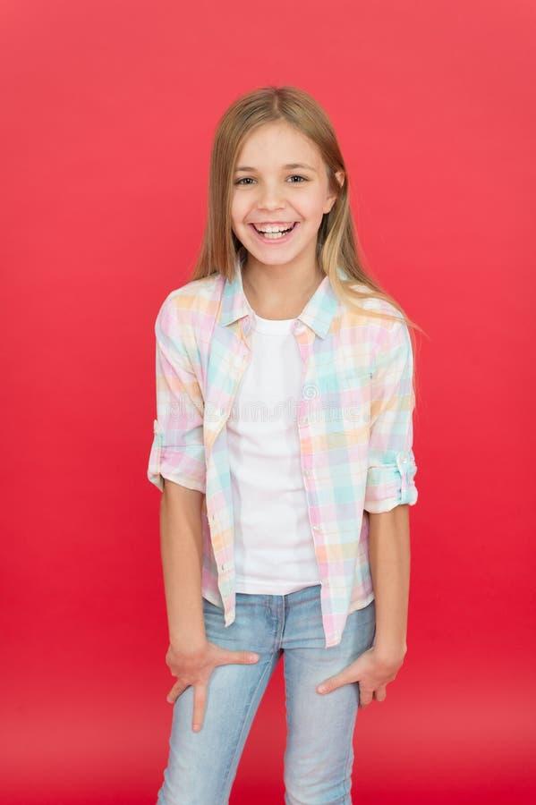 Sch?chterne Sch?nheit Gl?ckliche Kindheit Gesichtsausdruck des Mädchens lächelnder nettes Kinderauf rotem Hintergrund Positives G stockfotografie
