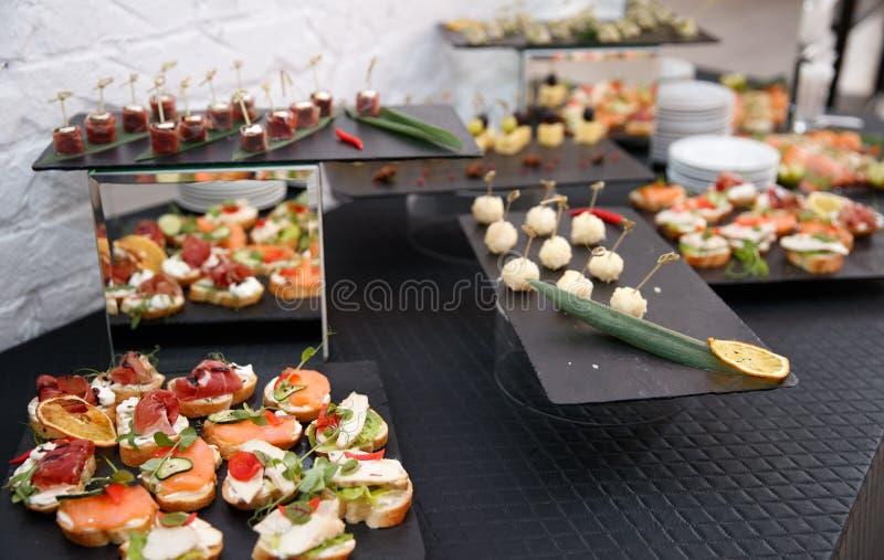 Sch?n verzierter versorgender Bankettisch mit verschiedenen Lebensmittelsn?cken und -aperitifs stockfotos