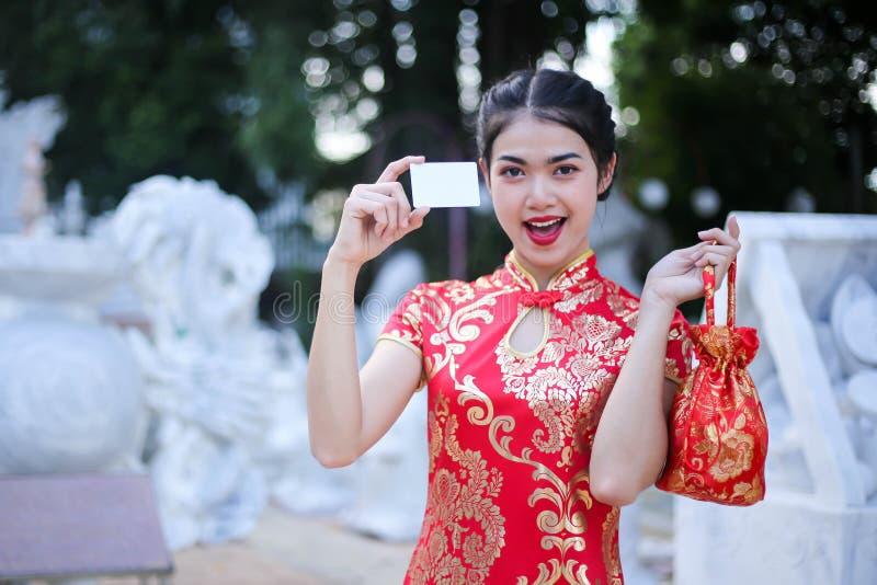 Sch?ne asiatische Frau, die Dollar oder Geld mit gl?cklichem Taschengeld, im Chinesischen Neujahrsfest h?lt Festlichkeiten, neues lizenzfreie stockfotografie