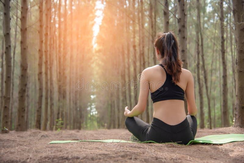 Sch?ne asiatische junge Frau, die auf gr?ner Matte liegt und Yoga in der Wald?bung und im Meditationskonzept tut Ruhig und Landsc stockfoto