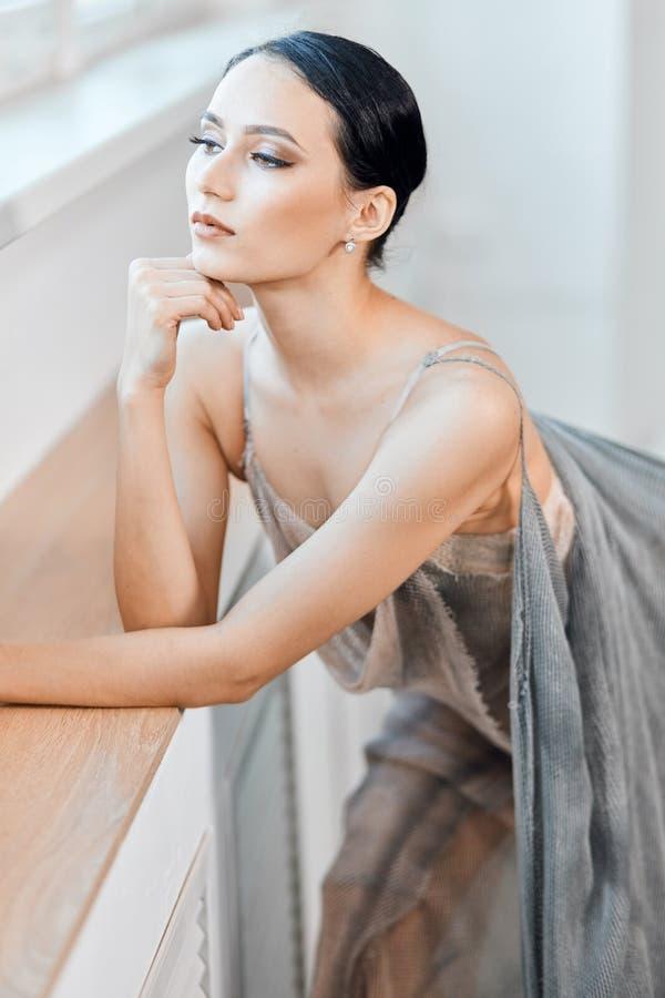 Sch?ne Ballerina im grauen losen langen transparenten Portr?t des Stadiums Kleider lizenzfreie stockfotografie
