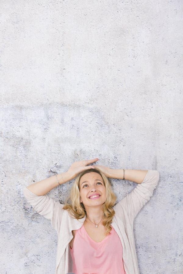 Sch?ne, blonde Frau zeigt auf und wirft vor Grau, Betonmauerhintergrund auf stockfoto