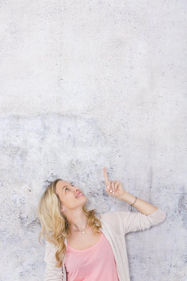 Sch?ne, blonde Frau zeigt auf und wirft vor Grau, Betonmauerhintergrund auf stockbild