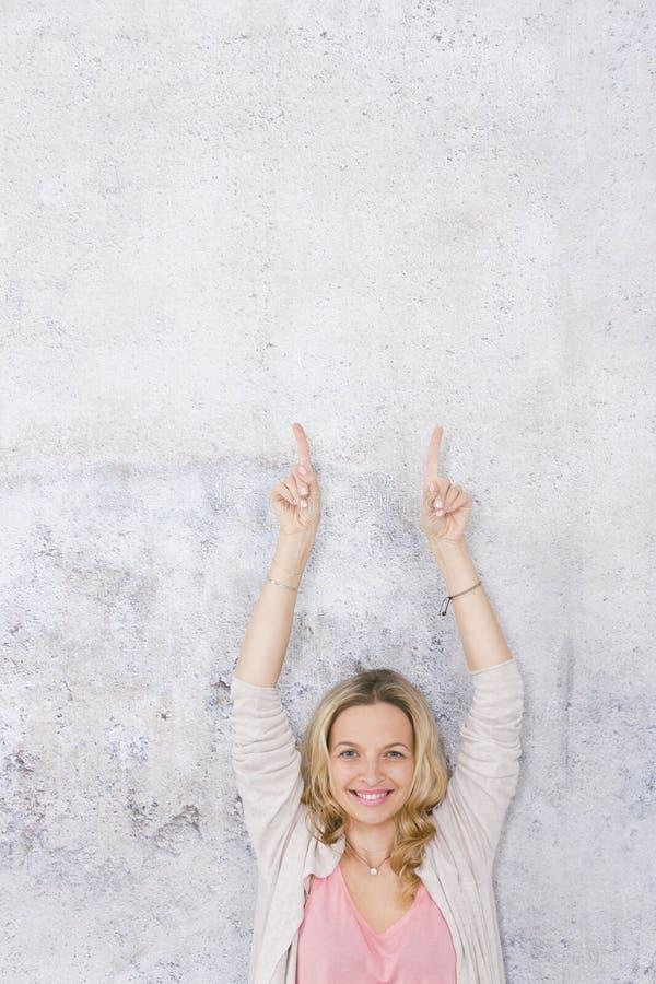 Sch?ne, blonde Frau zeigt auf und wirft vor Grau, Betonmauerhintergrund auf stockfotos