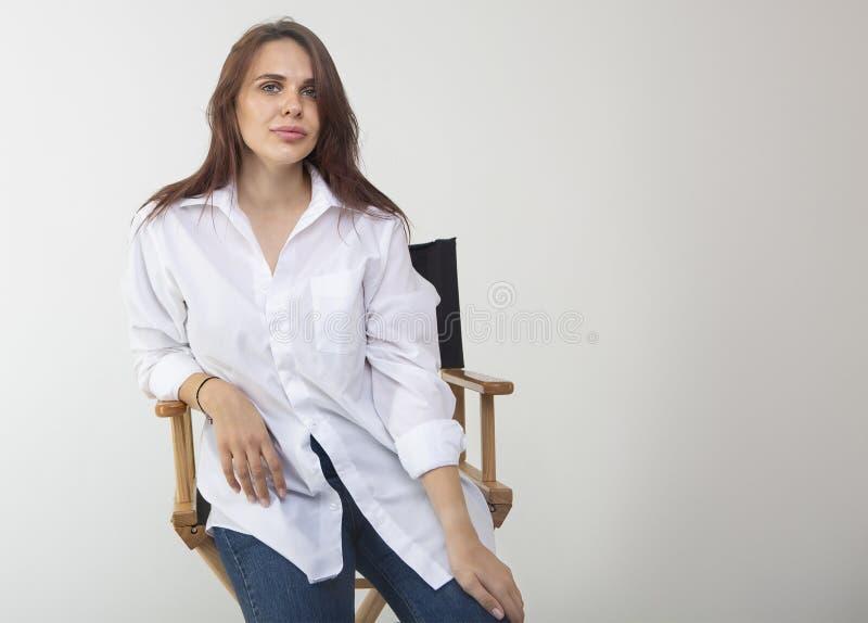 Sch?ne brunette Frau, die am Studio im wei?en Hemd aufwirft stockfoto