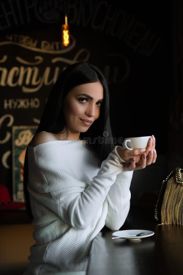 Sch?ne brunette Frau im Caf? mit Tasse Kaffee stockfotografie