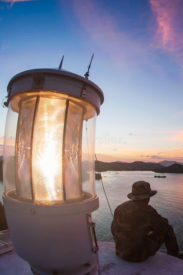 Sch?ne Draufsicht des Leuchtturms in der D?mmerung Leuchtturmmann, der auf Terrasse beim Betrachten von fantastischen Wolken mit  lizenzfreie stockbilder