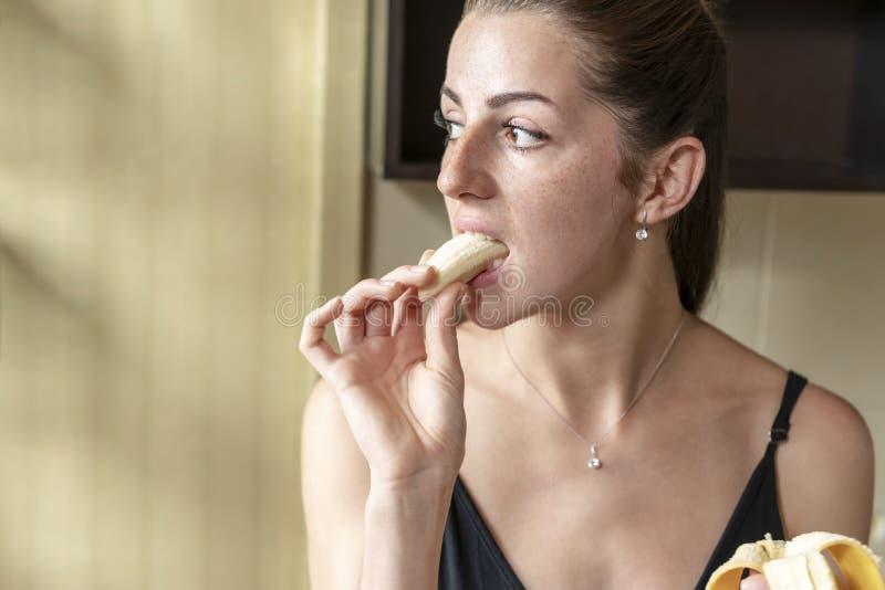 Sch?ne Frau, die Banane isst lizenzfreies stockfoto