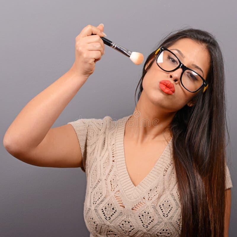 Sch?ne Frau, die Verfassung auf Gesicht mit kosmetischem Pinsel tut Mode-Modell, das gegen grauen Hintergrund aufwirft lizenzfreie stockfotografie