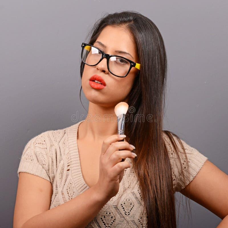 Sch?ne Frau, die Verfassung auf Gesicht mit kosmetischem Pinsel tut Mode-Modell, das gegen grauen Hintergrund aufwirft stockfoto