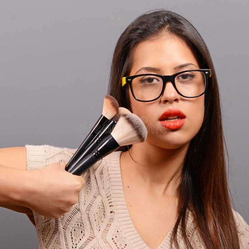 Sch?ne Frau, die Verfassung auf Gesicht mit kosmetischem Pinsel tut Mode-Modell, das gegen grauen Hintergrund aufwirft stockbilder