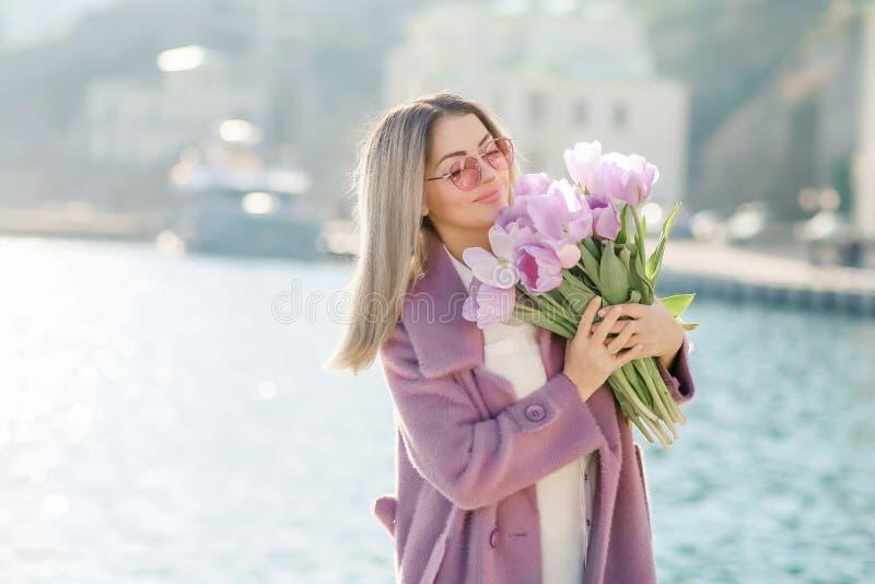 Sch?ne gl?ckliche Frau mit dem geraden Haar, das einen Blumenstrau? von rosa Tulpen ein sonniger Tag des Fr?hlinges h?lt stockfotos