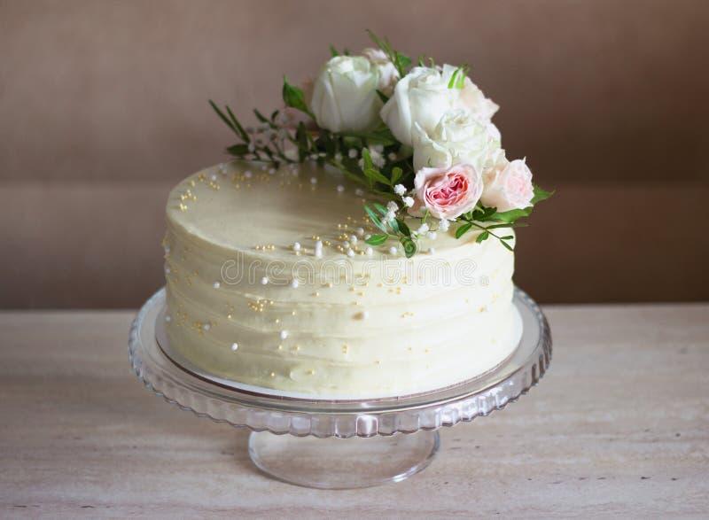 Sch?ne Hochzeitstorte mit Blumen auf Marmortabelle und wei?em Hintergrund lizenzfreies stockbild