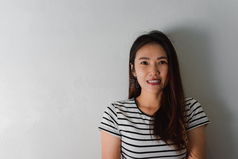 Sch?ne junge asiatische Frau, die auf Wandhintergrund l?chelt stockfoto