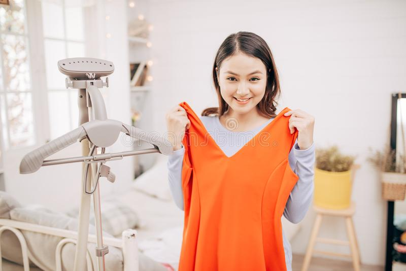 Sch?ne junge asiatische Frau, die mit der Kleidung versucht auf dem Kleid oben passt mit modernem im Raum l?chelt stockfotos