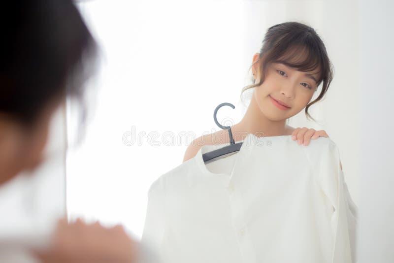 Sch?ne junge asiatische Frau, die mit der Kleidung versucht auf dem Kleid oben passt mit modernem und schauendem Reflexionsspiege stockbild
