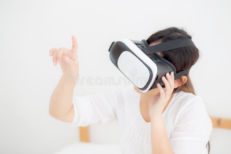 Sch?ne junge asiatische Frau nett und Kopfh?rer Spa? tragender vr virtueller Realit?t, M?dchenger?t und aufpassendes Simulatorspi lizenzfreies stockfoto