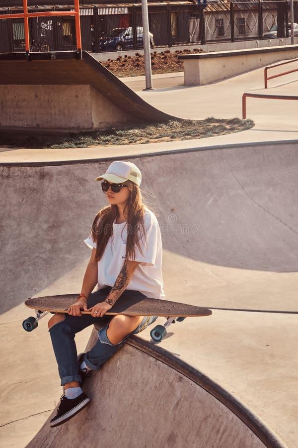 Sch?ne junge Frau in den sunglacces und in der Kappe sitzt am skatepark stockfotos