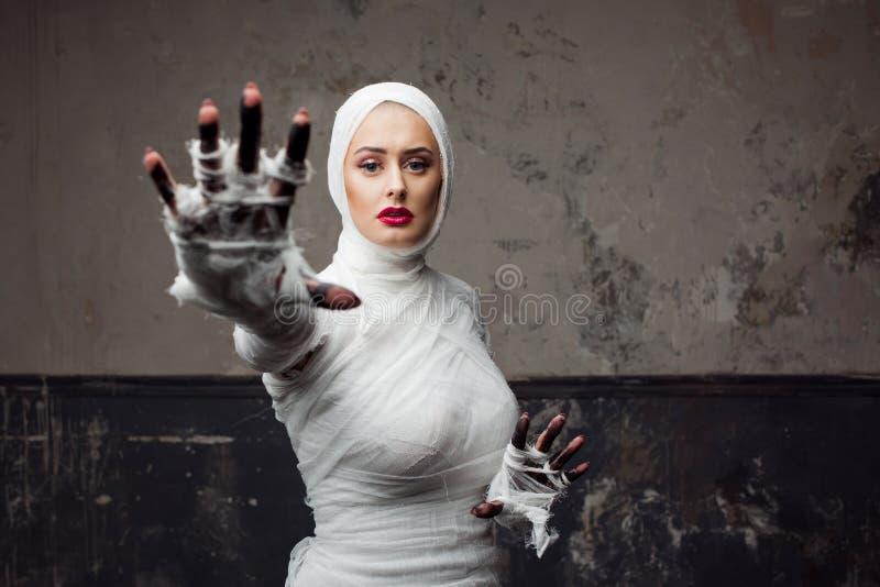 Sch?ne junge Frau in den Verb?nden M?dchen in einem Mamakost?m, Hand ziehend lizenzfreies stockbild