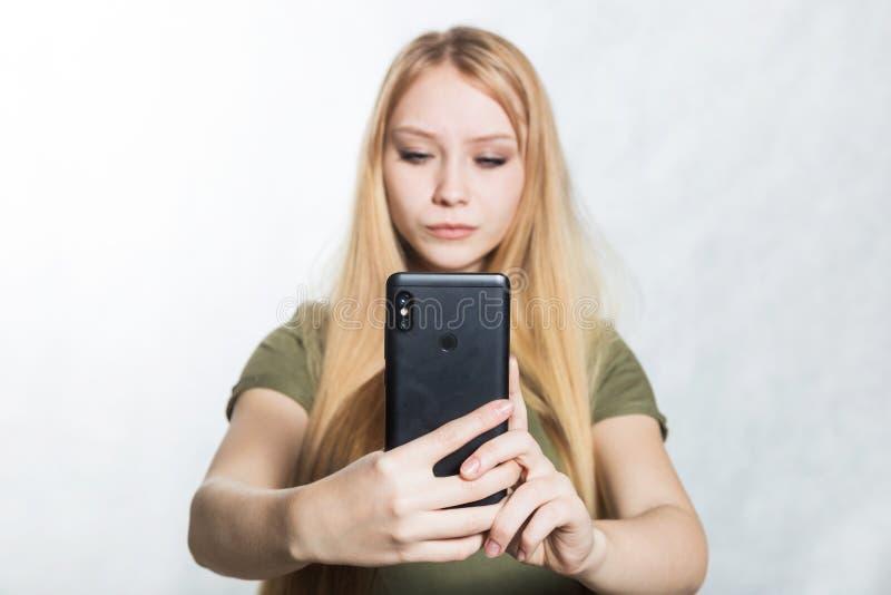 Sch?ne junge Frau, die Fotos auf einem Smartphone macht lizenzfreie stockfotos