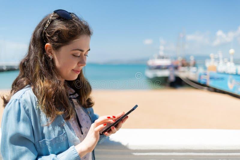 Sch?ne junge Frau, die Handy verwendet Meer und Schiffe auf dem Hintergrund Kopieren Sie Platz Konzept der modernen Technologie u stockfoto