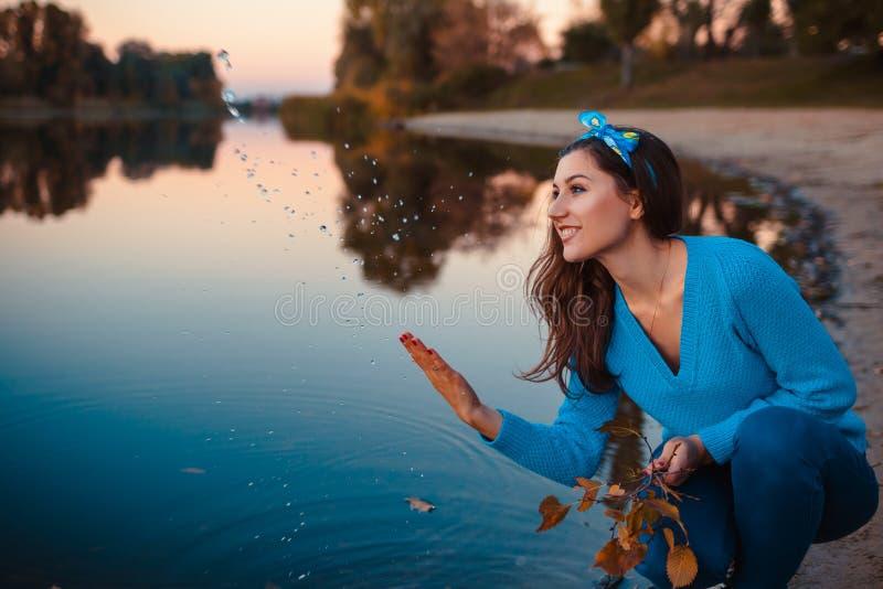 Sch?ne junge Frau, die am Herbstflussbankspritzwasser sitzt und Niederlassungen h?lt lizenzfreies stockbild