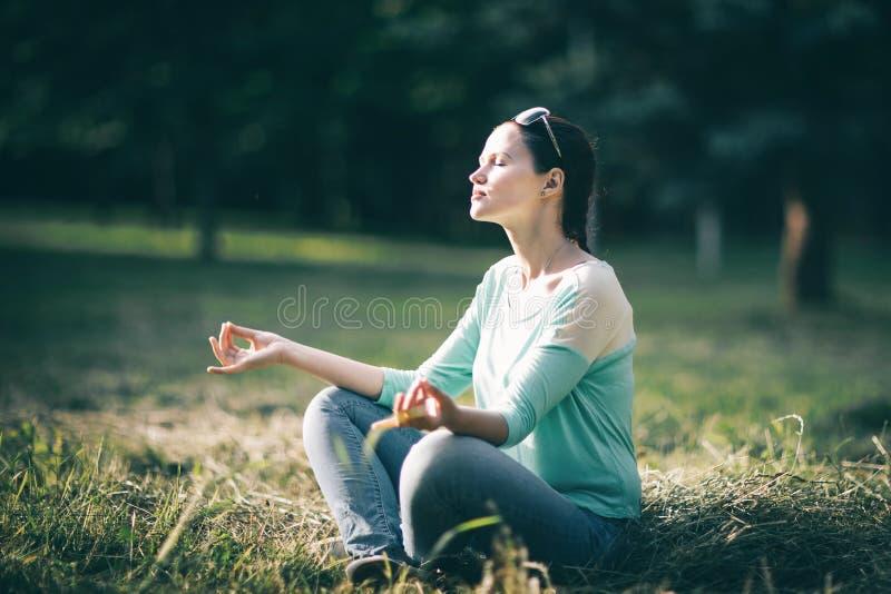 Sch?ne junge Frau, die im Lotussitz sitzt auf dem Rasen meditiert lizenzfreies stockbild