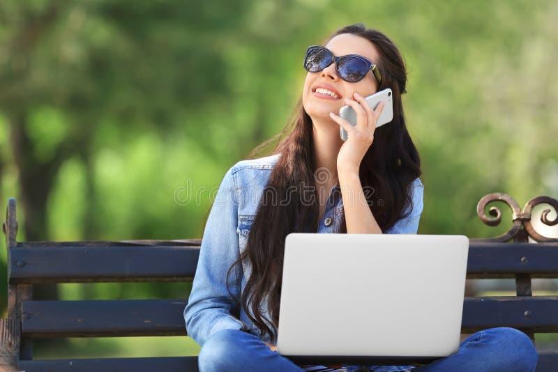 Sch?ne junge Frau, die im Park mit Laptop und Handy stillsteht stockbilder