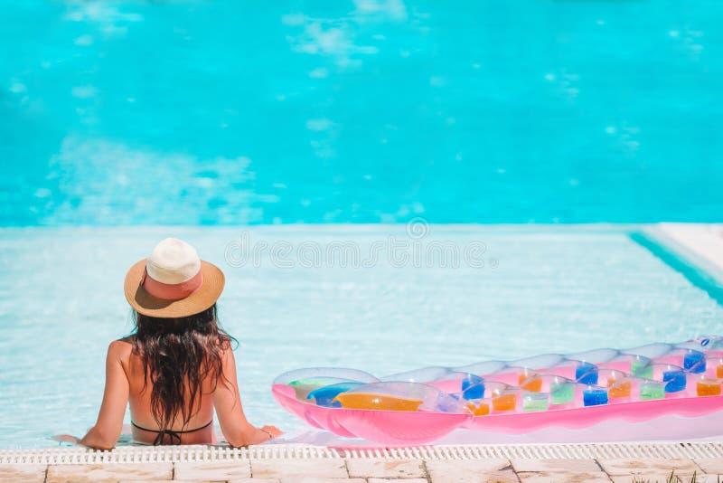 Sch?ne junge Frau, die im Swimmingpool sich entspannt lizenzfreie stockbilder