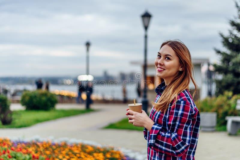 Sch?ne junge Frau, die Kaffeetasse h?lt und im Park l?chelt lizenzfreie stockfotografie