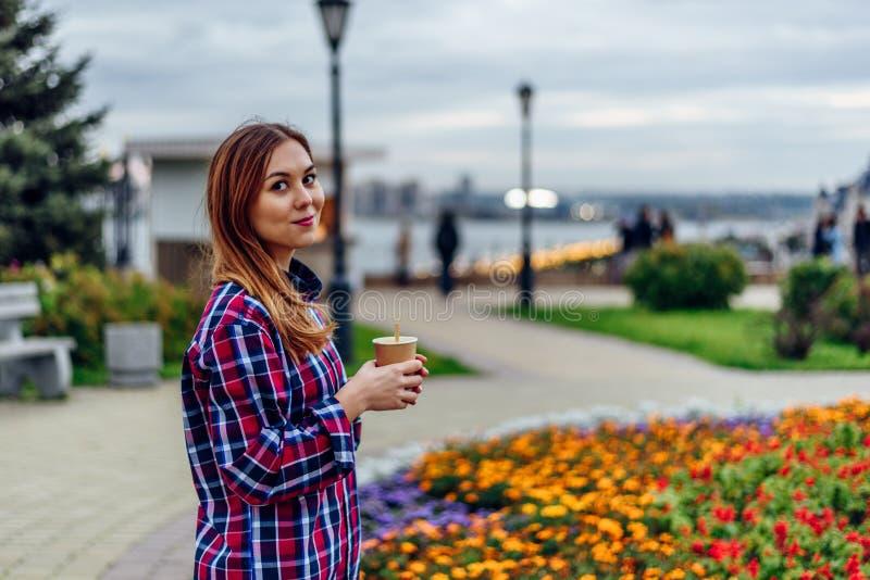 Sch?ne junge Frau, die Kaffeetasse h?lt und im Park l?chelt lizenzfreies stockbild