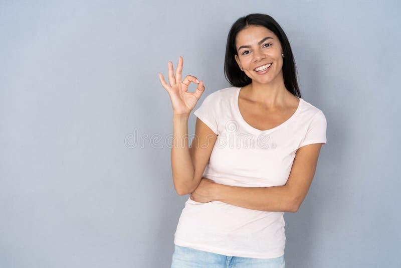 Sch?ne junge Frau, die okayzeichen zeigt stockfotos