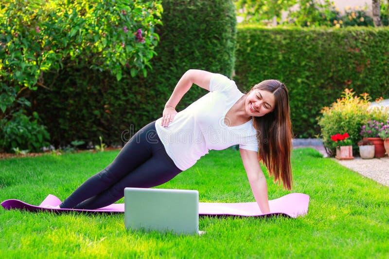 Sch?ne junge Frau, die Sport im Garten drau?en folgt F?hrer des Online-Tutorials oder Trainer auf Laptop tut lizenzfreie stockbilder