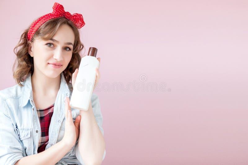 Sch?ne junge Frau mit Stift-obenmake-up und -frisur mit Reinigungswerkzeugen auf rosa Hintergrund lizenzfreie stockbilder
