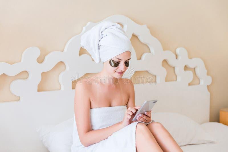 Sch?ne junge Frau mit Unteraugenklappen und der Anwendung von Handy oder Schreiben sms Massage im Bademantel, der im Bett liegt G lizenzfreies stockfoto