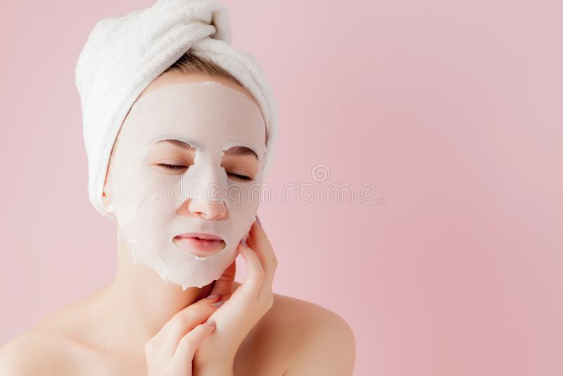 Sch?ne junge Frau wendet eine kosmetische Gewebemaske auf einem Gesicht auf einem rosa Hintergrund an stockbild