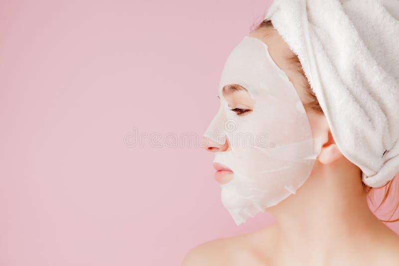 Sch?ne junge Frau wendet eine kosmetische Gewebemaske auf einem Gesicht auf einem rosa Hintergrund an Gesundheitswesen- und Sch?n stockbild