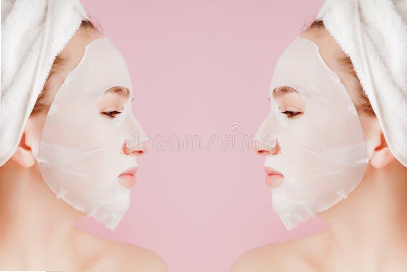 Sch?ne junge Frau wendet eine kosmetische Gewebemaske auf einem Gesicht auf einem rosa Hintergrund an Gesundheitswesen- und Sch?n lizenzfreie stockbilder