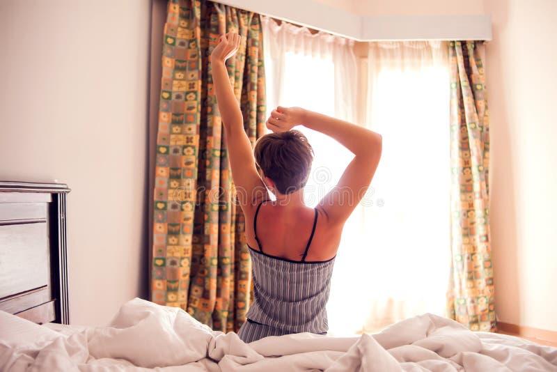 Sch?ne junge l?chelnde Frau, die auf Bett sitzt und morgens am Schlafzimmer ausdehnt stockbild